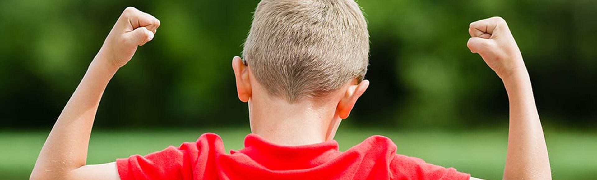 Niño con camisa roja celebra con los brazos